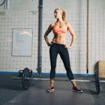 Full length portrait of muscular young woman standing at gym looking away with barbells on floor. Strong crossfit female at gym.